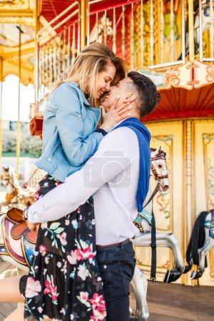 Foto de Feliz pareja joven con su novia en el carrusel - Imagen libre de derechos