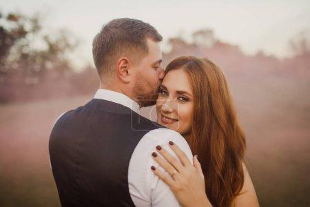 Photo pour Heureux couple de mariage câlins et baisers sur le fond de la ville - image libre de droit