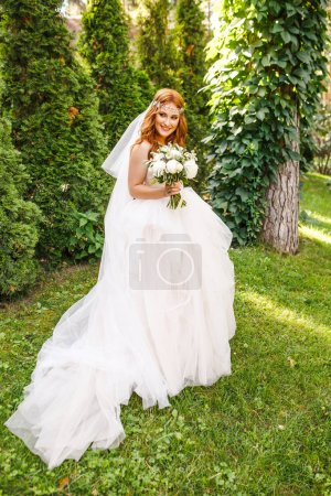 Photo pour Belle mariée en robe blanche posant dans le parc - image libre de droit