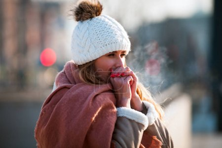 Young woman trying warming hands in cold winter day