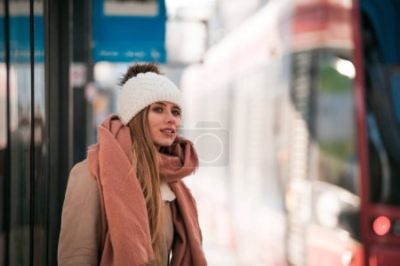 Photo pour Jeune femme en attente de tram à l'arrêt de bus de ville - image libre de droit