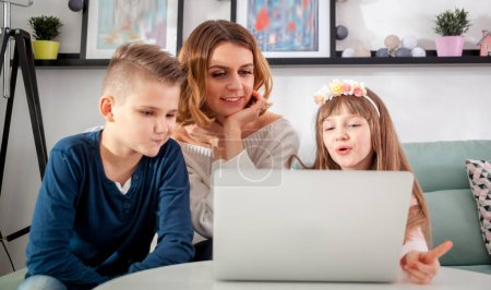 Young mother with children using laptop at home