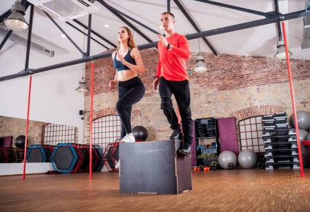 Sporty young couple doing squats on box at fitness gym