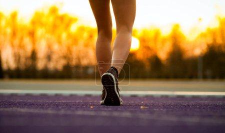 Legs of athlete woman running on racetrack on stadium track