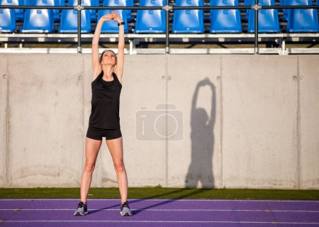 Photo for Young athletic woman stretching on stadium running track before jogging - Royalty Free Image