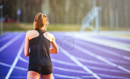 Photo for Back view of athletic woman starting training on running track - Royalty Free Image