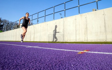 Young athletic woman running on stadium track