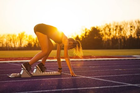 Young athletic woman on running track starting from start line