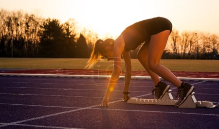 Photo for Young athletic woman on running track starting from start line - Royalty Free Image
