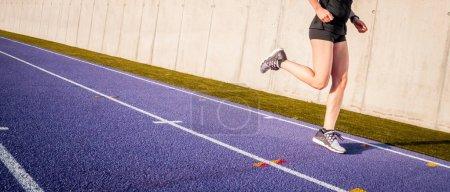 Photo pour Jambes de femme athlète qui court sur la piste de course sur piste de stade - image libre de droit
