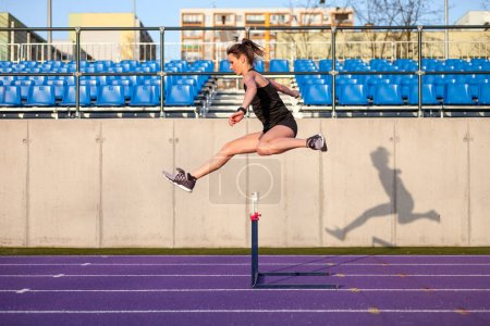 Athletic woman running on stadium track and jumping above hurdle