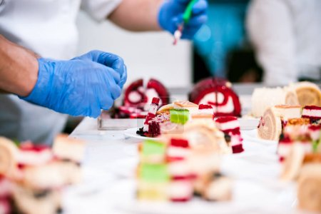Close view of confectioner preparing cakes in pastry shop