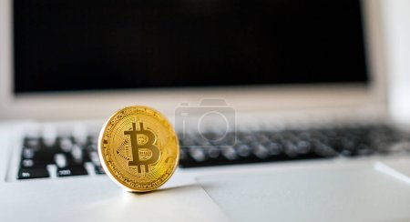 Close view of bitcoin coin on laptop background