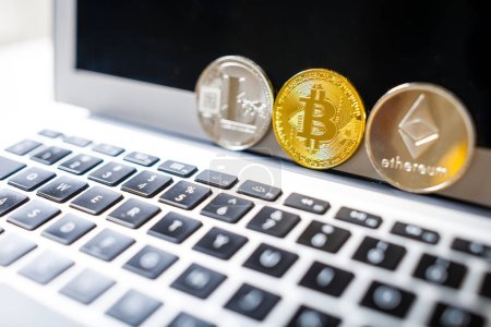 Bitcoin, Litecoin and Ethereum coins in row on laptop