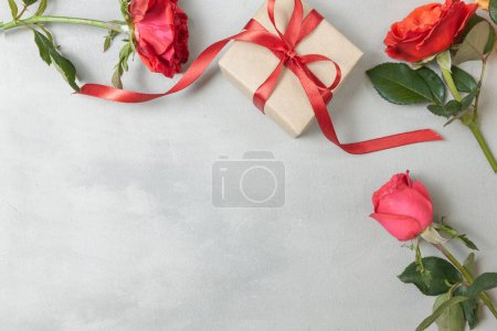 Red rose flowers, gift box or present on gray ston...