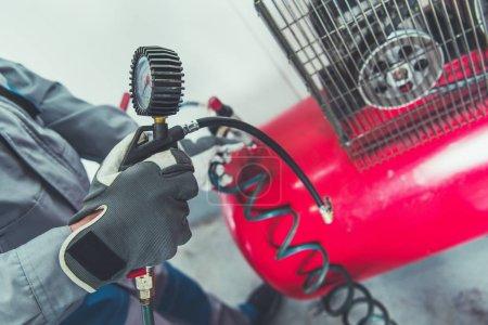 Photo pour Compresseur d'Air de garage. Réglage de la pression dans les pneus d'une voiture. - image libre de droit