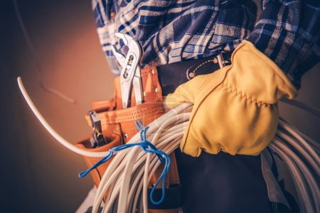 Photo for Electrician with Electric Cable Preparing For Installation in the Newly Constructed Building. - Royalty Free Image
