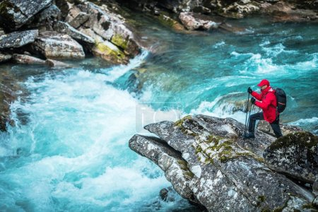 Hiker and the Glacial River. Caucasian Men in Front of the Rushing River.