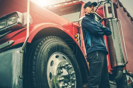 Photo pour American Trucker Fiers. Conducteur de semi-camion devant sa machine impressionnante. Industrie des transports Thème . - image libre de droit