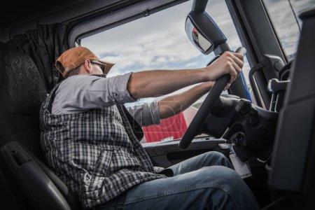 Photo pour Camionneur caucasien dans sa trentaine derrière la roue semi-camion moderne. Industrie des transports . - image libre de droit