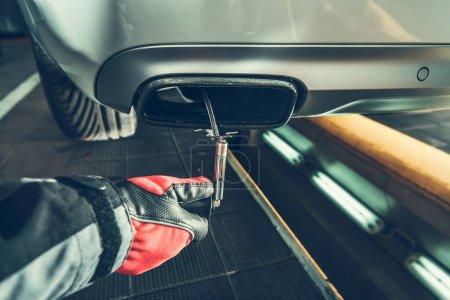 Photo pour Diesel Smoke Emission Testing Equipment in Hand of Mechanic. Pousser le capteur dans le silencieux de voiture . - image libre de droit