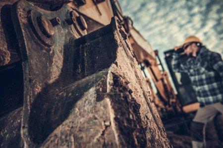 Photo pour Travaux de terrassement. Pelle Fermeture du seau de fer et le travailleur en arrière-plan - image libre de droit