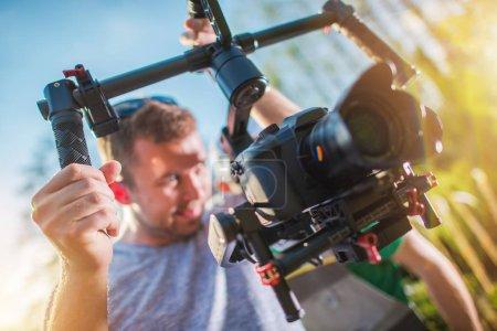 Photo pour Reflex numérique vidéo caméra sur un cardan. Cameraman caucasien de la caméra installée sur le stabilisateur de professionnel. - image libre de droit