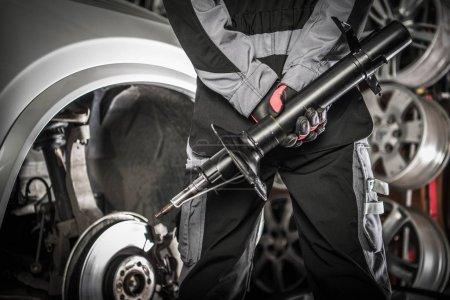 Photo pour Concept automobile. Garagiste avec dispositif hydraulique amortisseur en mains se préparer au changement nécessaire absorbeurs. - image libre de droit