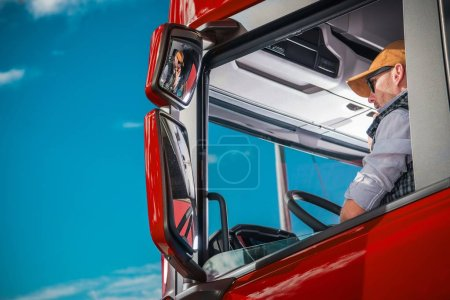 Photo for Transportation Industry Theme. Caucasian Truck Driver in His 30s Inside the Red Semi Cabin. - Royalty Free Image