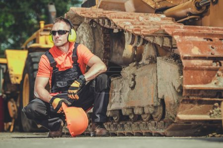 Photo for Heavy Duty Equipment Mechanic Side by Side with Aged Bulldozer. Industrial Concept. - Royalty Free Image