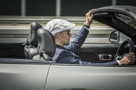 Photo for Convertible Car Freedom Drive. Caucasian Driver in His 30s Wearing Stylish Beret Behind the Wheel of Modern Cabriolet Vehicle. - Royalty Free Image