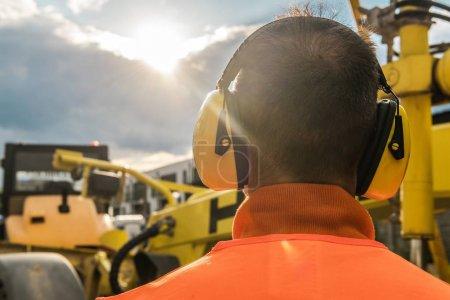 Photo pour Équipement de construction de réduction du bruit. Travailleur caucasien avec des écouteurs de protection d'audition. - image libre de droit