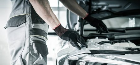 Photo pour Mécanicien de voiture regardant sous le capot de véhicule recherchant un problème. Thème de service automatique. Industrie automobile. - image libre de droit