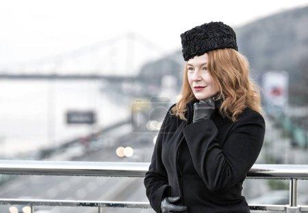 Aged women model in black coat and gloves on bridg...