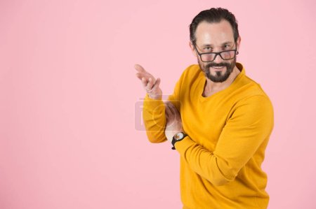 Un hombre inteligente con gafas en la nariz en concepto de por qué. ¿Por qué haces una pregunta? El hombre responde a la pregunta. Chico preguntándote con la mano aislada en estudio sobre fondo rosa
