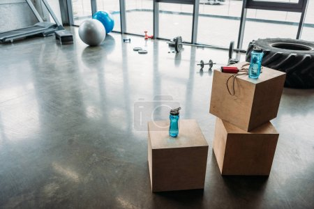 jump rope and bottles of water on wooden boxes, dumbbells, barbell, training tire, fitness balls, step platform and treadmill at gym
