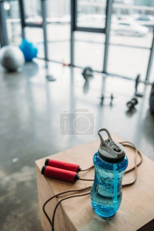 closeup view of jump rope and bottle of water on wooden box at gym