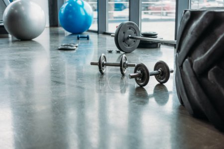 barbell, dumbbells, fitness balls and training tire on floor at gym