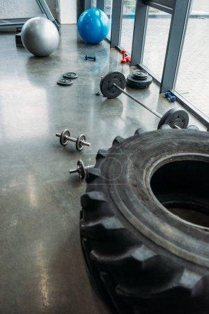 Photo pour Balles de fitness, haltères différentes, haltère, tapis roulant et pneu d'entraînement à la salle de gym - image libre de droit