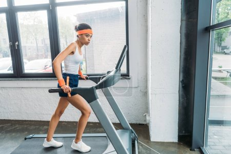 african american female athlete running on treadmill at gym