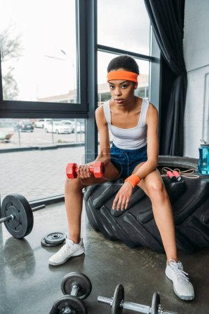 african american sportswoman in headband and wristbands doing exercise with dumbbell while sitting on training tire at gym