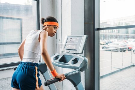 young african american female jogger running on treadmill at gym