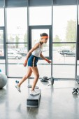 young african american sportswoman doing aerobics step at gym