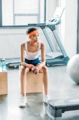 african american sportswoman in headband and headbands resting on wooden box at gym