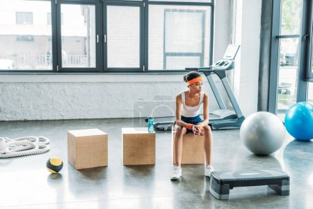 young female athlete sitting on wooden box at gym