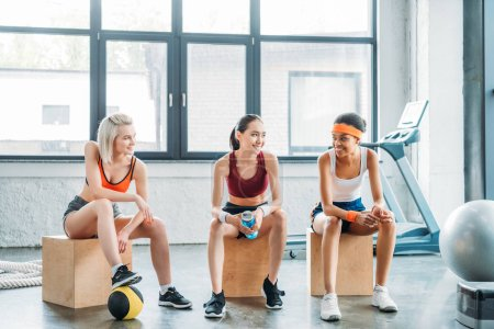 happy multiethnic female athletes talking to each other and sitting on wooden boxes at gym