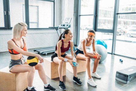 young attractive multicultural sportswomen sitting on wooden boxes at gym