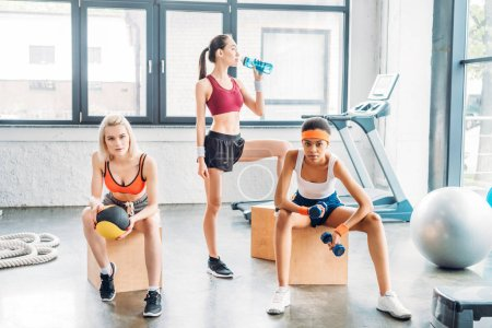 young asian sportswoman drinking water while two female athletes exercising and sitting on wooden boxes at gym