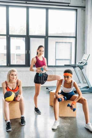 three multicultural sportswomen on wooden boxes with ball, dumbbells and bottle at gym
