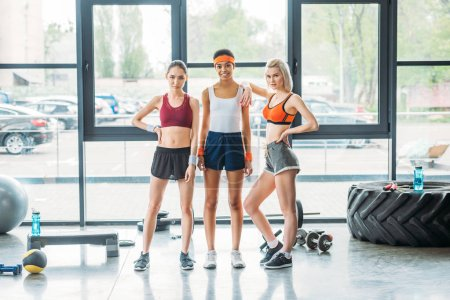 young attractive multiethnic sportswomen posing at gym